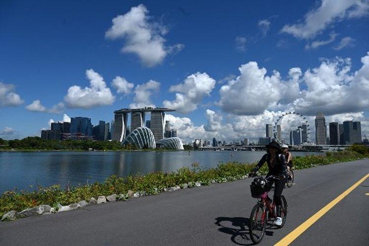 Pengendara sepeda berjalan di depan gedung distrik bisnis keuangan di Singapura pada 28 Juni 2021.