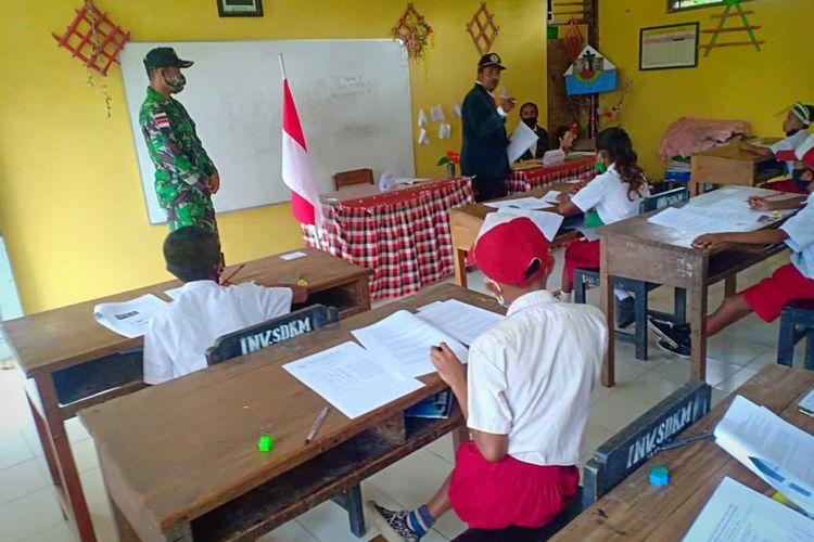 Anggota TNI Satuan Tugas Pengamanan Perbatasan Indonesia-Timor Leste dari Pos Yonarmed 6/3 Kostrad, membantu menjadi pengawas ujian akhir semester (UAS), Selasa (4/5/2021)