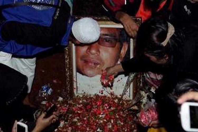 Ustaz Jeffry Al Buchori saat dimakamkan di Tempat Pemakaman Umum Karet Bivak, Jakarta Pusat, Jumat (26/4/2013) . Para pelayat mengiringi dengan doa dan taburan bunga. Ustaz yang akrab disapa Uje ini meninggal akibat kecelakaan tunggal.