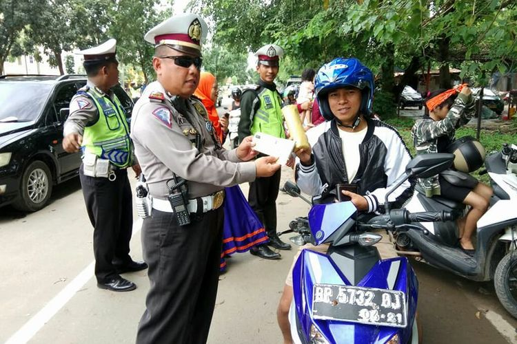 Salah seorang petugas Satlantas Polresta Barelang memberikan handuk kecil kepada pengendara sepeda motor yang taat aturan dalam operasi Zebra Siligi hari keenam di Batam