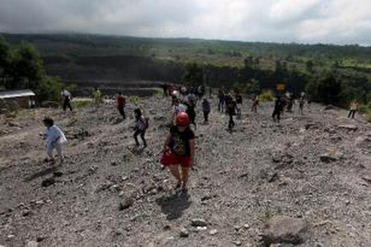 Wisatawan mengunjungi Kali Gendol, Cangkringan, Sleman, DI Yogyakarta, saat mengikuti wisata lava tour di kaki Gunung Merapi, Jumat (17/5/2013). Wisata mengunjungi daerah bekas aliran lava erupsi Merapi ini dipungut biaya Rp 300.000 - Rp 500.000 per trip.