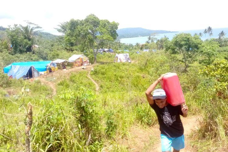 Seorang pengungsi korban gempa memikul jerigen berisi air bersih untuk dibawa ke lokasi pengungsian di hutan Tahola, Desa Passo, Kecamatan Baguala Ambon, Selasa (15/10/2019)