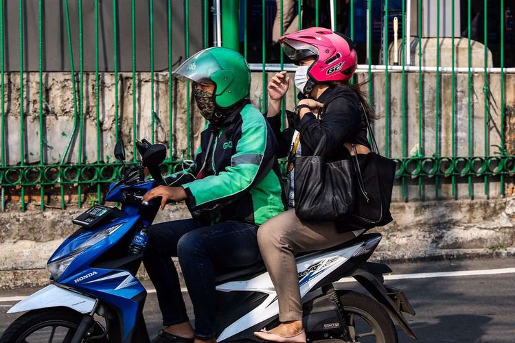 Pengemudi ojek online dengan penumpangnya melintas di Kawasan Stasiun Sudirman, Jakarta Pusat, Senin (8/6/2020). Pemerintah Provinsi DKI Jakarta mengizinkan pengemudi ojek online beroperasi untuk mengangkut penumpang selama PSBB transisi dengan menerapkan protokol kesehatan.