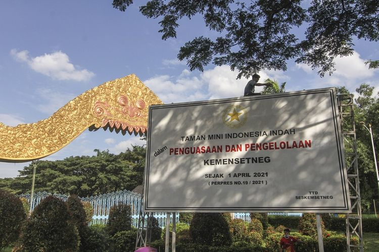 Pekerja memasang pelang bertuliskan TMII dalam penguasaan dan pengelolaan Kemensetneg di depan gerbang TMII, Jakarta, Rabu (7/4/2021). Pemerintah melalui Kementerian Sekretariat Negara (Kemensetneg) mengambil alih pengelolaan Taman Mini Indonesia Indah (TMII) dari Yayasan Harapan Kita. ANTARA FOTO/Asprilla Dwi Adha/foc.