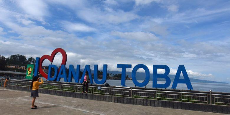 Wisatawan berfoto di Dermaga Parapat Danau Toba, Simalungun, Sumatera Utara, Minggu (4/11/2018). Menpar Arief Yahya menyatakan Danau Toba menjadi prioritas pertama pemerintah pusat sebagai Kawasan Strategi Pariwisata Nasional (KSPN), bersama Labuan Bajo (NTT), Mandalika (Lombok), dan Borobudur (Jateng), yang diharapkan menjadi destinasi wisatawan internasional. ANTARA FOTO/Andika Wahyu/