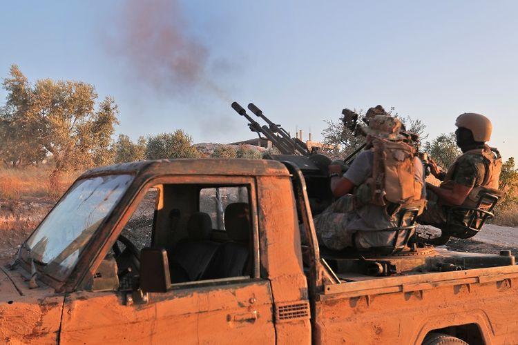 Anggota dari kelompok Hayat Tahrir al-Sham (HTS) yang merupakan bekas afiliasi Al Qaeda Suriah, melepaskan tembakan dari atas kendaraan bak terbuka di Idlib selatan Suriah.
