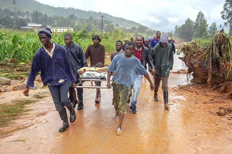 Seorang lelaki yang diselamatkan dibawa menggunakan tandu oleh rekan-rekannya di Kota Ngangu, Chimanimani, Manicaland, Zimbabwe, setelah daerah itu dilanda topan Idai, Senin (18/3/2019). Ratusan orang tewas dan lainnya hilang di Mozambik dan Zimbabwe setelah topan Idai membawa serta banjir bandang dan angin kencang, 17 Maret lalu.