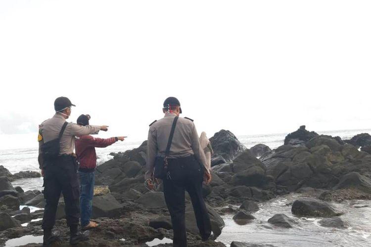 Sejumlah anggota polisi meninjau lokasi korban terseret ombak di Pantai Jayanti, Cidaun, Cianjur, Jawa Barat, Selasa (25/5/2020) petang. Kedua korban asal Kecamatan Sukaresmi, Cianjur itu berhasil diselamatkan petugas balawisata setempat.