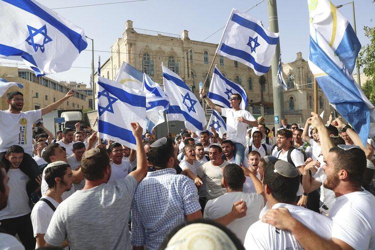 Dalam foto arsip 10 Mei 2021 ini, warga Israel mengibarkan bendera nasional selama parade Hari Yerusalem, di Yerusalem.