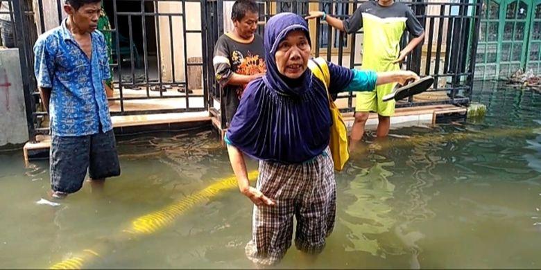 Gus (66), warga Gang Subur Lama, menunjukkan ketinggian banjir yang menggenangi rumahnya sejak 1,5 bulan yang lalu. Puluhan rumah terendam dan warga mulai pindah.
