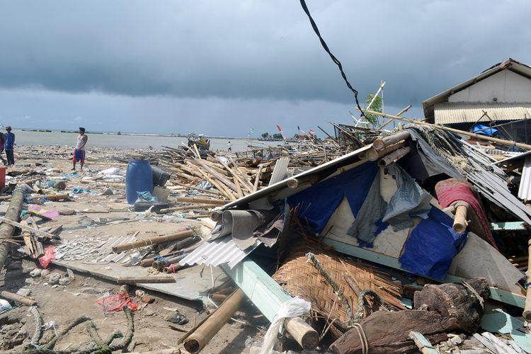 Warga melintas di Tempat Pelelangan Ikan (TPI) yang rusak akibat tsunami Selat Sunda di Kampung Nelayan, Labuan, Pandeglang, Banten, Selasa (25/12/2018). BNPB (Badan Nasional Penanggulangan Bencana) melaporkan hingga Selasa (25/12) pagi jumlah korban meninggal dunia akibat tsunami Selat Sunda mencapai 481 orang, 1.216 orang luka, dan 67 orang lainya dinyatakan masih hilang. ANTARA FOTO/Muhammad Bagus Khoirunas/aww.