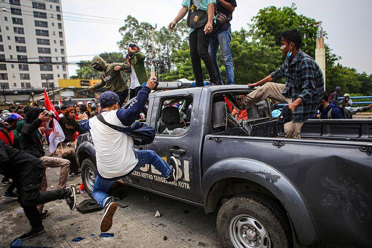 Sejumlah pengunjuk rasa menyerang mobil polisi di Jalan Daan Mogot, Kota Tangerang, Banten, Kamis (8/10/2020). Aksi tersebut sebagai bentuk perlawanan atas penahanan massa yang akan menuju gedung DPR untuk menggelar aksi penolakan pengesahan Undang-Undang Cipta Kerja.