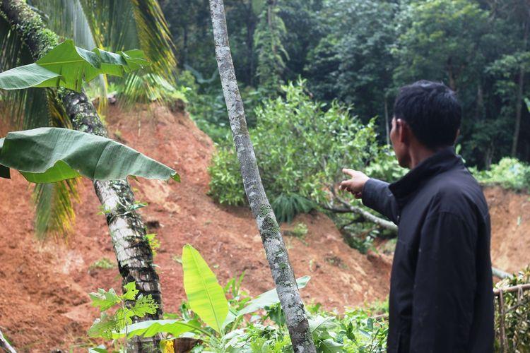 Seorang warga memerlihatkan kondisi lereng di belakang perkampungan di Desa Karangnunggal, Kecamatan Cibeber, Kabupaten Cianjur, Jawa Barat, yang masih labil pasca longsor, Minggu (22/3/2020).
