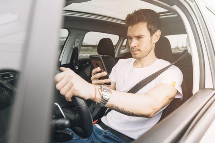 Ilustrasi orang menyetir sambil main handphone