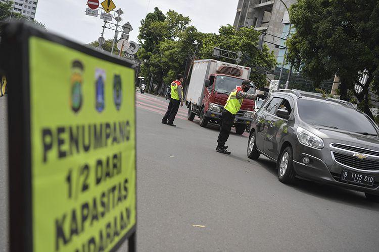 Polisi melakukan imbauan kepada pengendara mobil untuk dapat mematuhi penerapan Pembatasan Sosial Berskala Besar (PSBB) di kawasan Menteng, Jakarta (11/4/2020). Iimbauan ini dilakukan agar masyarakat menerapkan pembatasan sosial berskala besar (PSBB) selama 14 hari, yang salah satu aturannya adalah pembatasan penumpang kendaraan serta anjuran untuk menggunakan masker jika berkendara.