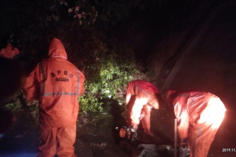 Petugas BPBD Agam dan Kecamatan Tanjung Raya, Agam membersihkan material longsor di kelok 3 yang menyebabkan akses jalan terputus, Senin (25/11/2019) dini hari