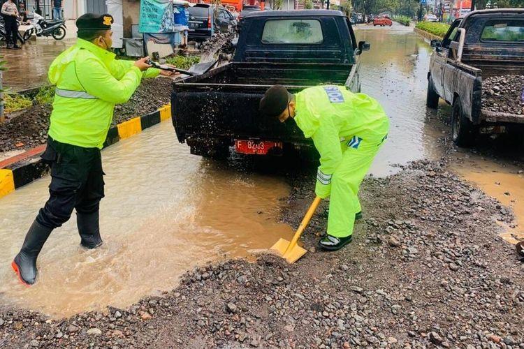 Sejumlah anggota polisi membersihkan material lumpur dan pasir yang terbawa banjir yang menggenangi ruas jalan protokol di Cianjur, Jawa Barat, Selasa (21/4/2020)