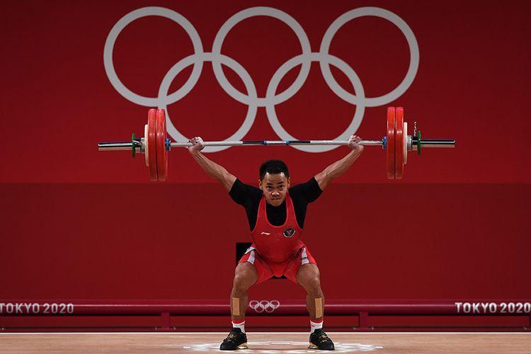 Lifter Indonesia Eko Yuli Irawan melakukan angkatan snatch dalam kelas 61 kg putra Grup A Olimpiade Tokyo 2020 di Tokyo International Forum, Tokyo, Jepang, Minggu (25/7/2021). Eko Yuli berhasil mempersembahkan medali perak dengan total angkatan 302 kg.