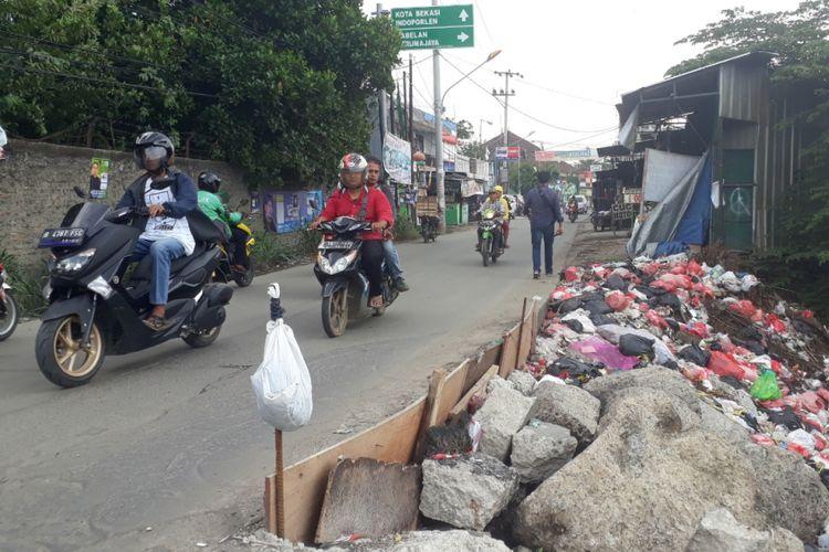 Tampak jalan Raya Karang Satria, Kabupaten Bekasi, yang rawan amblas kerap membahayakan pengendara yang melintas, Selasa (27/11/2018).