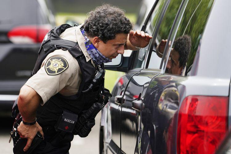 Seorang polisi melongok ke dalam mobil yang terparkir di luar Pentagon, Selasa, 3 Agustus 2021. Terjadi penembakan pada Selasa pagi waktu setempat dekat pintu masuk Pentagon, dengan seorang polisi dilaporkan tewas.