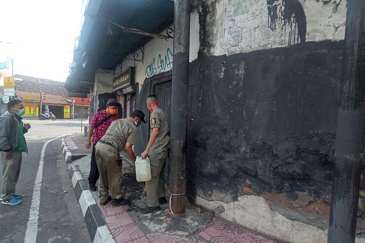 Pol PP saat menghapus vandalisme di sekitar simpang empat Wirobrajan, Jumat (10/9/2021)