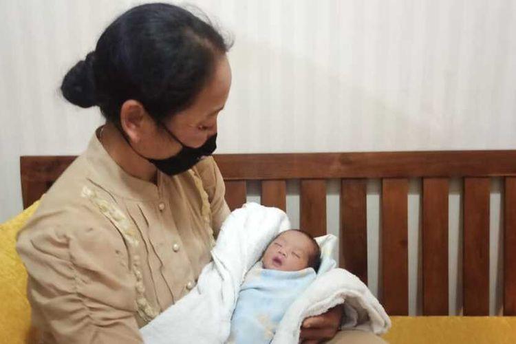 GENDONG—Salah seorang ibu menggendong bayi perempuan yang ditemukan di teras rumah warga Jalan Menur, Kelurahan Ronowijayan, Kecamatan Siman, Kabupaten Ponorogo, Jawa Timur
