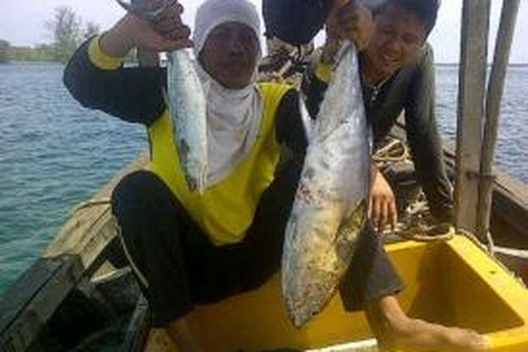 Pemancing memamerkan hasil tangkapan tuna dan tenggiri