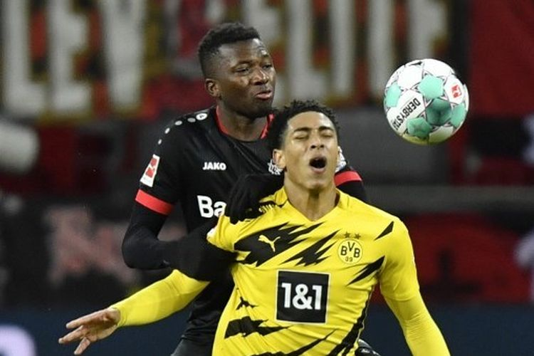 Bek Bayer Leverkusen, Edmond Tapsoba (belakang), berduel dengan pemain Borussia Dortmund, Jue Bellingham (kanan), pada laga lanjutan pekan ke-17 Bundesliga di Stadion Bay-Arena, Rabu (20/1/2021) dini hari WIB.