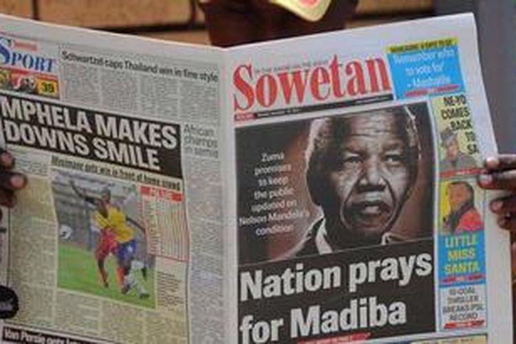 Seorang warga Afsel membaca koran yang brita utamanya adalah kabar kesehatan Nelson Mandela. Madiba yang tertulis di koran itu adalah nama panggilan tradisional untuk Nelson Mandela.