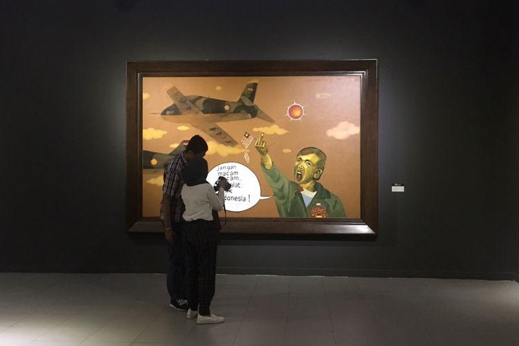 Pengunjung sedang melihat hasil foto di pameran Dua Kutub, di Galeri Nasional Indonesia, Jakarta, Kamis (11/1/2018).