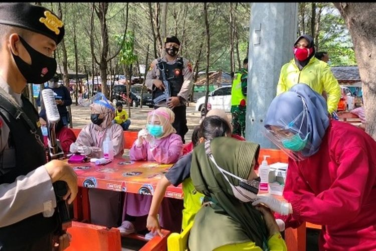 Petugas kesehatan bersama kepolisian saat pelaksanaan swab dan vaksinasi bagi pedagang dan wisatawan luar daerah di OW PAI, tempat wisata terbesar di Kota Tegal, Jawa Tengah, Sabtu (12/6/2021).