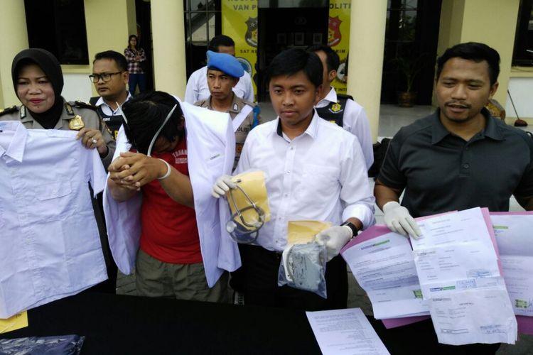 Dokter gadungan dan barang bukti diamankan di Polrestabes Surabaya.