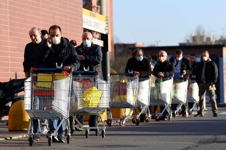 Warga memakai masker mengantre di supermarket pada hari kedua lockdown Italia. Gambar diambil di Pioltello, dekat Milan, Rabu (11/3/2020).