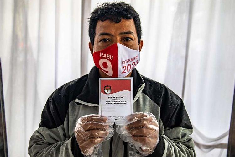 Foto dirilis Minggu (6/12/2020), memperlihatkan seorang warga dengan mengenakan masker dan sarung tangan plastik yang telah disediakan penyelenggara menunjukkan surat suara saat mengikuti Simulasi Pemungutan dan Penghitungan Suara Pemilihan Bupati dan Wakil Bupati Semarang 2020 di Bergas, Kabupaten Semarang, Jawa Tengah.