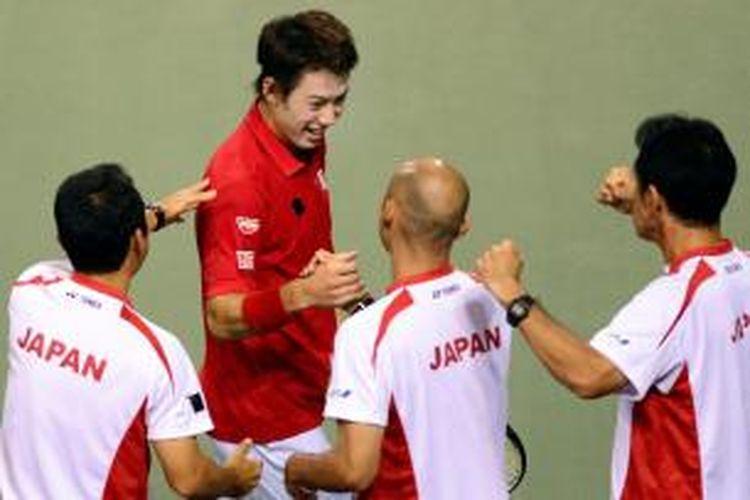 Petenis Jepang, Kei Nishikori (merah) mendapat ucapan selamat dari timnya, setelah memenangi pertandingan pertama melawan Alejandro Falla dari Kolombia, pada play-off Grup Dunia, Davis Cup, Jumat (13/9/2013).