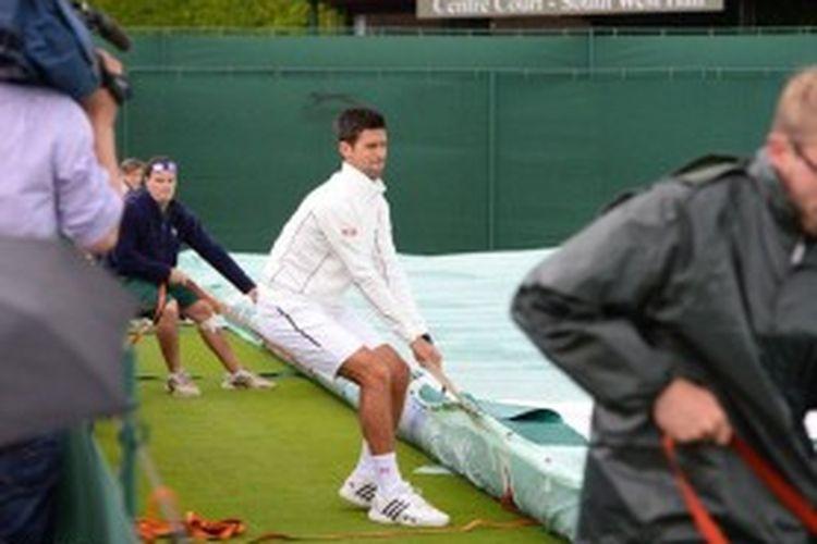 Petenis Serbia, Novak Djokovic menarik penutup lapangan bersama para petugas turnamen grand slam, Wimbledon. Djokovic sedang berlatih di court 5, saat hujan turun dan memaksanya berhenti, Sabtu (22/6/2013).