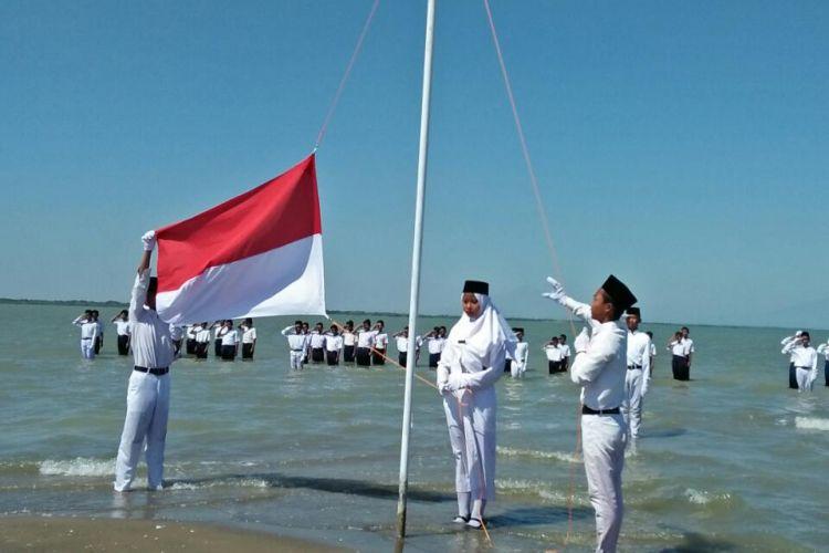 Petugas pengibar bendera menaikan sang merah putih,  dalam upacara peringatan HUT Kemerdekaan RI ke 73 di Pantai Onggojoyo,  Kecamatan Wedung,  Kabupaten Demak,  Jateng,  Jumat (17/8/2018)