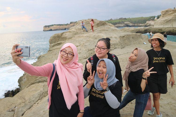 Wisatawan berfoto selfie di atas karang Pantai Klayar, Pacitan, Jawa Timur, Selasa (28/1/2020).