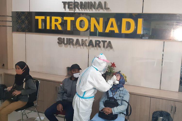 Petugas medis mengambil sampel dari dalam hidung penumpang dalam swab antigen di Terminal Tipe A Tirtonadi Solo, Jawa Tengah, Kamis (24/12/2020).