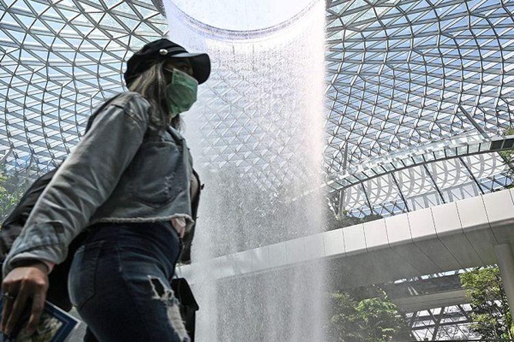 Seorang pengunjung terlihat memakai masker ketika melintas di depan air terjun Rain Vortex di Jewel yang berlokasikan di Bandara Internasional Changi
