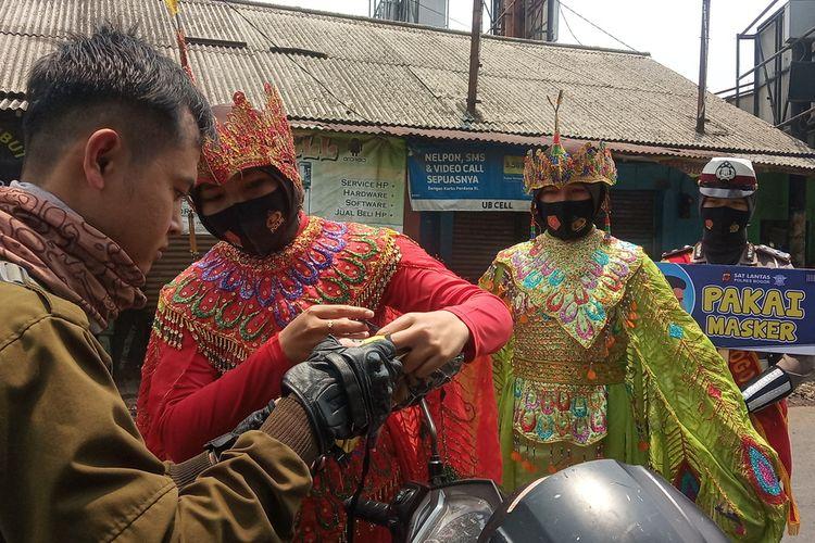 Petugas Kepolisian memberi masker kepada pengendara sepeda motor di Jalan Raya Bogor, Cibinong, Kabupaten Bogor, Jawa Barat, Selasa (15/9/2020)