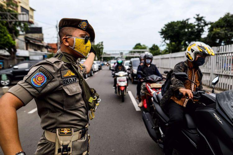Petugas satuan polisi pamong praja saat patroli penegakan aturan pembatasan sosial berskala besar (PSBB) di Jl. Matraman Raya, Kecamatan Jatinegara, Jakarta Timur, Selasa (19/5/2020). Dalam kegiatan patroli PSBB tersebut, target penegakan untuk masyarakat yang tidak mengunakan masker dijalanan.