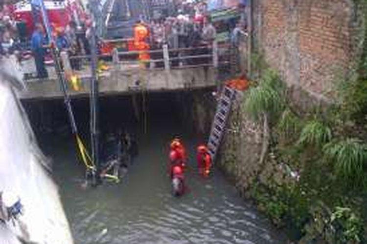 Petugas dari DPPK Kota Bandung saat melakukan evakuasi bangkai mobil Grand Livina yang hanyut terbawa banjir di Sungai Citepus, Jalan Pasirkoja, Bandung, Selasa (25/10/2016). KOMPAS.com/DENDI RAMDHANI