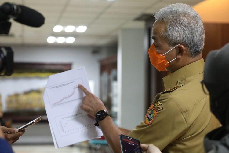 Gubernur Jawa Tengah (Jateng) Ganjar Pranowo menunjukkan grafik penurunan kasus Covid-19 kepada para awak media saat menghadiri Rapat Koordinasi (Rakor) Percepatan Penanganan Covid-19 di Lantai 2 Kantor Sekretariat Daerah (Setda) Provinsi Jateng, Senin (15/2/2021).