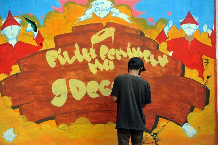 Peserta menggambar mural bertema sosialisasi Pilkada Serentak 2020 di Nanggalo, Padang, Sumatera Barat, Sabtu (29/8/2020). KPU Sumbar bekerja sama dengan Padang Grafiti United menggelar Lomba Grafiti dan Mural dalam rangka mensukseskan Pilkada Serentak 9 Desember 2020 dengan tetap menjalankan protokol kesehatan COVID-19. ANTARA FOTO/Iggoy el Fitra/wsj.