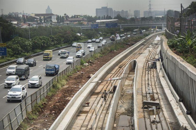 Kendaraan melintas di samping proyek pembangunan kereta ringan atau Light Rail Transit (LRT) rute Cibubur-Cawang di Tol Jagorawi, Cibubur, Jakarta, Kamis (10/8/2017). Pengerjaan proyek pembangunan LRT Jabodetabek yang meliputi tiga rute, yaitu  rute Cibubur-Cawang sepanjang 14,5 km telah mencapai 37 persen, rute Bekasi Timur-Cawang sepanjang 17,1 km telah mencapai 17 persen sementara rute Cawang-Dukuh Atas sepanjang 10,5 km baru mencapai tiga persen. ANTARA FOTO/Aprillio Akbar/aww/17.