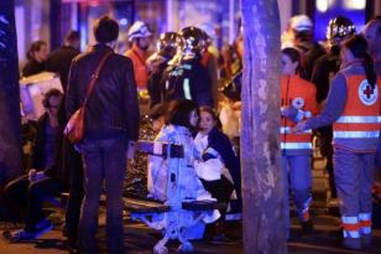 Korban serangan teroris dievakuasi di Paris, 13 November 2015. Lebih dari 100 orang tewas dalam aksi penembakan dan bom yang dilakukan oleh teroris pada 13 November malam.