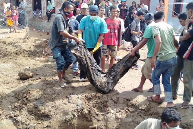 Warga mengangkut jenazah yang ditemukan saat menggali lubang septik tank di lahan pembangunan perumahan bersubsidi, pada Rabu (19/12/2018). Kerangka jenazah ini diyakini sebagai korban bencana gempa dan tsunami yang melanda aceh tahun 2004 lalu.*****