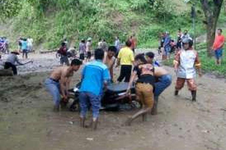 Foto : Warga sementara membantu mengevakuasi sepeda motor yang terjebak dalam timbunan lumpur dan longsor di ruas jalan Ponorogo-Pacitan Di Desa Wates, Kecamatan Slahung, Kabupaten Ponorogo, Kamis ( 12/1/2017).