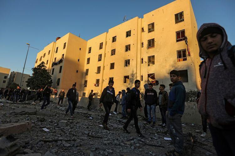 Warga Palestina berjalan di dekat gedung yang terkena serangan udara Israel di Beit Lahia, utara Jalur Gaza. Israel melancarkan serangan itu sebagai balasan atas tiga roket yang ditembakkan Hamas. (9/12/2017)